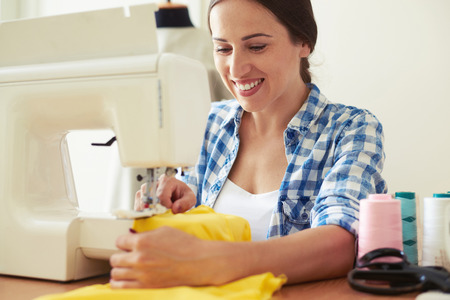 modiste: smiley young woman sewing yellow dress Stock Photo