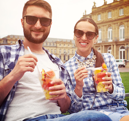 vacationers: urban photo of smiley couple with fruits