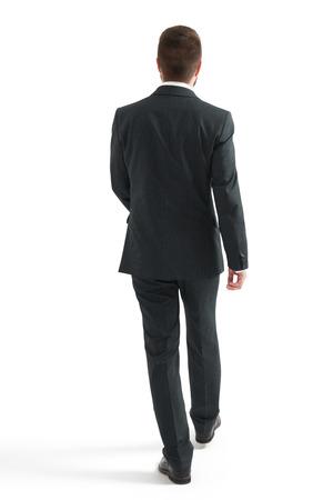 piernas hombre: Vista posterior de la marcha de negocios en traje negro. aislado en fondo blanco
