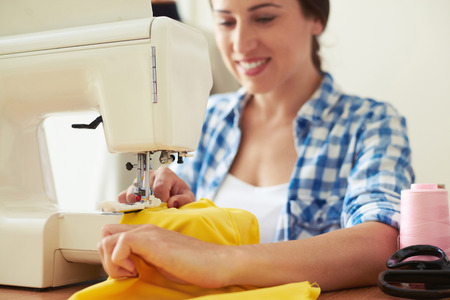 modiste: seamstress sewing yellow dress. focus on sewing-machine