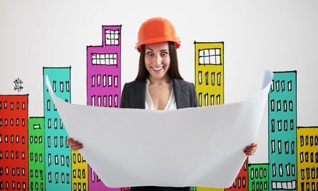 variegated: excited woman in orange hardhat with blueprint over grey wall with variegated drawing houses