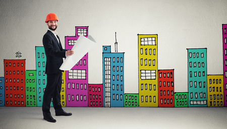 variegated: smiley man in orange hardhat with blueprint over grey wall with variegated drawing houses Stock Photo