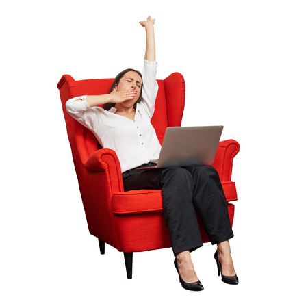 tedious: tired businesswoman sitting in red chair with laptop and yawning. isolated on white background