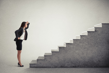 serious woman looking up at top of concrete stairway over light grey background Standard-Bild
