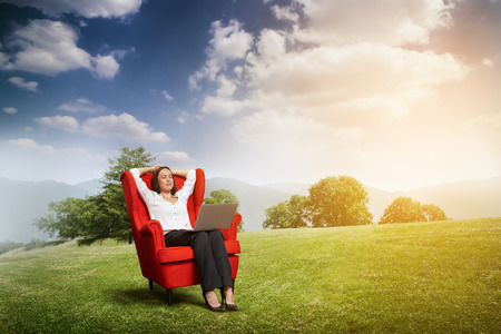 over hill: relaxed woman with closed eyes sitting on the red chair with laptop on green meadow over hill and blue sky Stock Photo