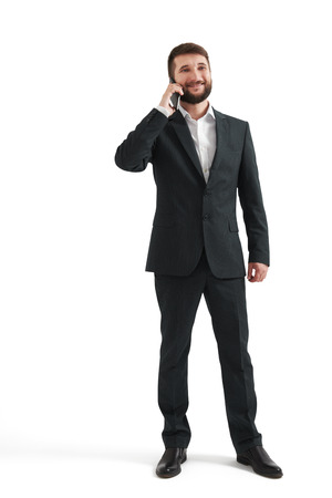 formal wear: smiley businessman in formal wear holding his smartphone near ear and smiling. isolated on white background Stock Photo