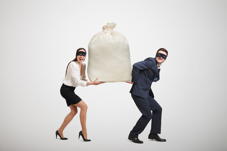 delinquency: laughing woman and man in formal wear and black mask on the eyes holding big bag and looking at camera. isolated on light grey background