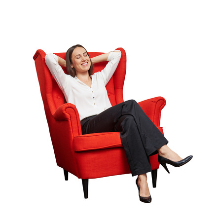 smiley happy woman with closed eyes sitting on red chair and dreaming. isolated on white background Foto de archivo