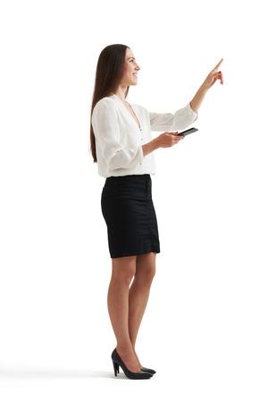 personen: zijaanzicht portret van zakenvrouw in formele slijtage bedrijf smartphone en wijst op iets. geïsoleerd op witte achtergrond