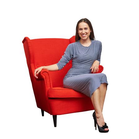 mujer sentada: mujer joven sonriente en traje sentado en la silla roja y mirando a la cámara. aislado en fondo blanco