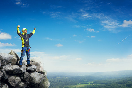 mountaineer: happy tourist on rock raising his hands up over beautiful landscape