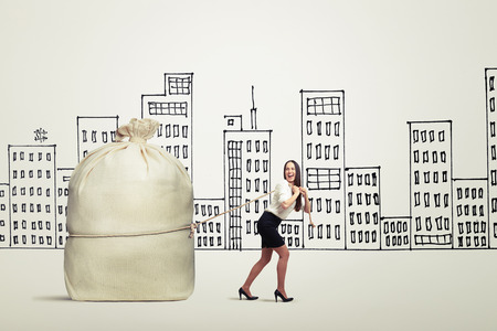 big woman: funny woman in formal wear pulling big bag over drawing city Stock Photo