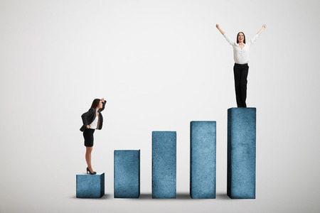 top down: businesswoman standing at the lower step of diagram and looking up at the winner over light grey background