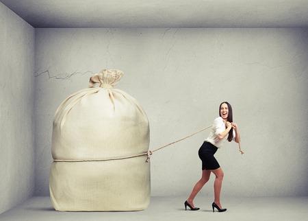 dragging: happy woman in formal wear pulling big bag in grey concrete room