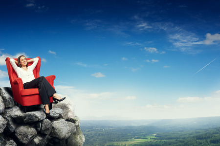 respite: smiley happy woman with closed eyes sitting on red chair on top of rock and dreaming over blue sky and beautiful landscape