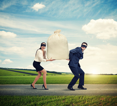 illegality: happy couple of thieves carrying bag and running on the road