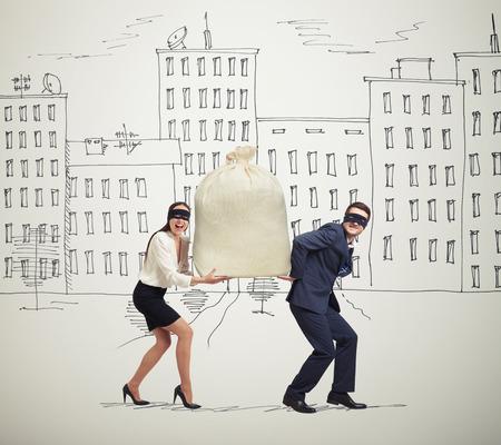 delincuencia: divertida imagen de la feliz pareja de ladrones que llevan el bolso y mirando a la cámara en la elaboración de la calle Foto de archivo