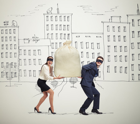 woman holding money: funny picture of happy couple of thieves carrying bag and looking at camera in drawing street Stock Photo