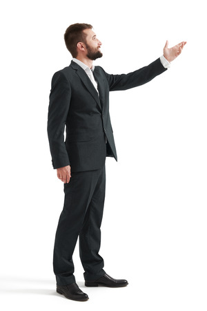 hand wear: full length portrait of businessman in formal wear pointing hand at something and looking at it. isolated on white background