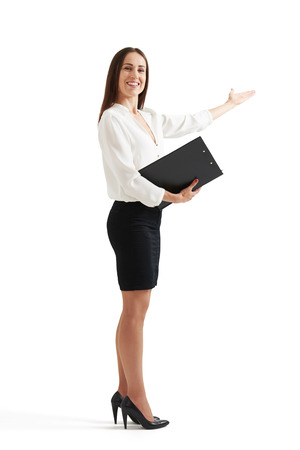 publicize: full length portrait of happy businesswoman with folder pointing her hand at something. isolated on white background