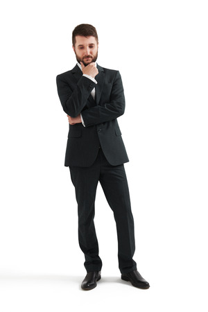serious thoughtful businessman in formal wear holding his hand at chin and looking down. isolated on white background Stock Photo