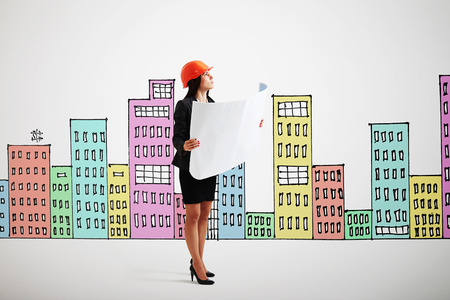 variegated: serious businesswoman in orange hardhat with blueprint looking up over background with variegated drawing houses