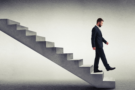 descend: smiley businessman in formal wear walking down the steps over grey background