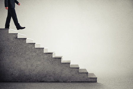 step: businessman in formal wear walking down the steps  over grey background Stock Photo