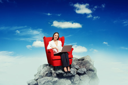 respite: smiley businesswoman with laptop on the red chair on top of rock over blue sky