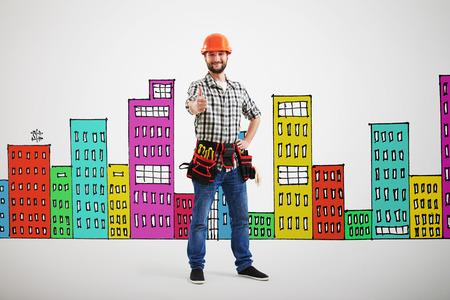 albañil: constructor sonriente que muestra los pulgares para arriba sobre la pared gris con las casas de dibujo abigarrado