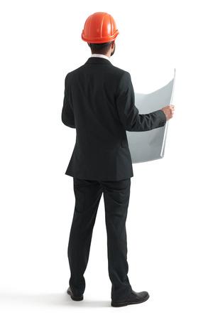 arquitecto: vista posterior de hombre de negocios en naranja casco celebración de planos. aislado en fondo blanco