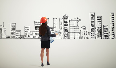 looking at view: back view of businesswoman in orange hardhat with blueprint looking at drawing houses Stock Photo