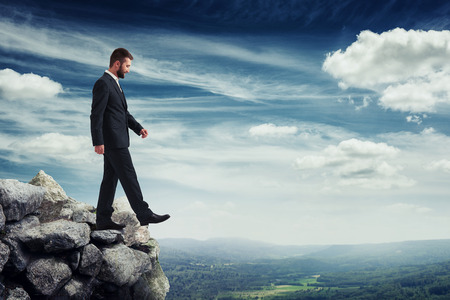 brink: smiley businessman walking on the brink of a precipice over blue sky