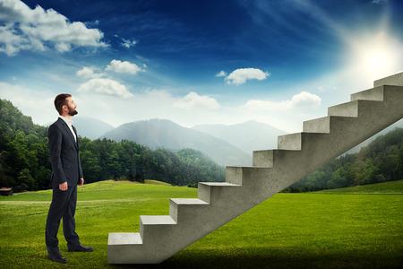 escaleras: hombre de negocios sonriente de pie en el prado verde y mirando a la escalera