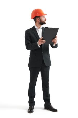 hombre con sombrero: hombre de negocios en ropa formal y casco naranja celebración de la carpeta negro y mirando algo. aislado en fondo blanco