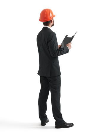 detras de: vista posterior de hombre de negocios en el casco anaranjado con la carpeta negro. aislado en fondo blanco