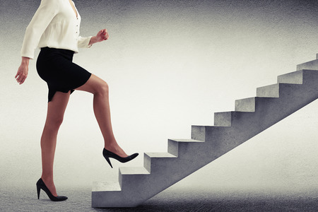 climbing ladder: businesswoman in formal wear walking up stairs over light grey background Stock Photo