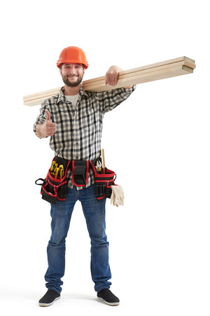 builder symbol: smiley builder in uniform showing thumbs up and holding long wooden boards. isolated on white background Stock Photo