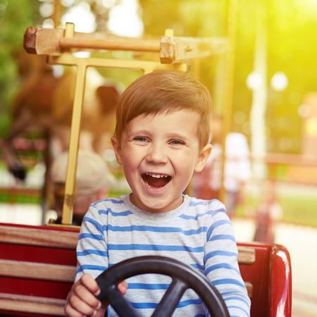 gelukkig jongetje het besturen van een auto op merry-go-round