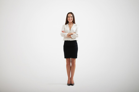 full-length portrait of smiley businesswoman in formal wear with folded hands over light grey background