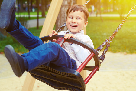 laughing little boy riding on a swing and looking at camera in a park Foto de archivo