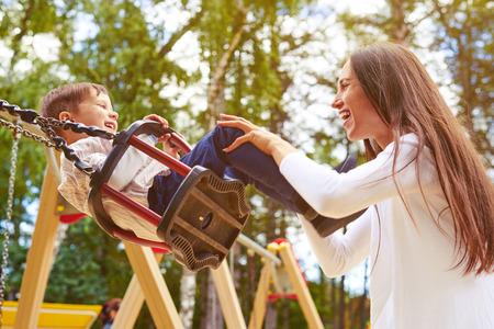 gelukkige moeder duwen lachen zoon op schommel in een park