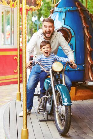 opgewonden man met een kleine jongen met plezier op motorfiets op merry-go-round Stockfoto