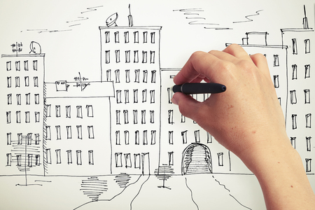 woman's hand: womans hand drawing houses on a paper