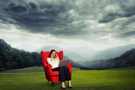 dark sky: tired businesswoman sitting on red chair over beautiful dark landscape with meadow and lowering sky Stock Photo