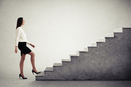 successful businesswoman in formal wear walking up concrete stairs over light grey background Фото со стока
