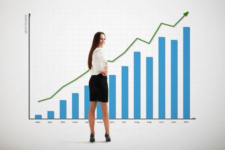 smiley businesswoman with big graph with positive dynamics over light grey background Stock Photo