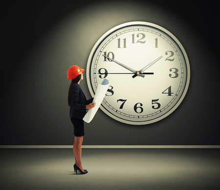 femme dessin: d'affaires sérieux dans l'horloge orange avec plan debout sur le mur gris avec grande horloge blanche
