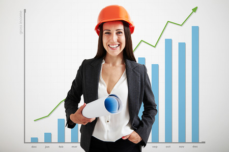 a helmet: portrait of happy woman architect in orange hardhat holding plan and looking at camera over graph with positive dynamics
