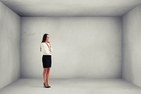despondent: despondent businesswoman thinking about something and looking down in grey empty room Stock Photo
